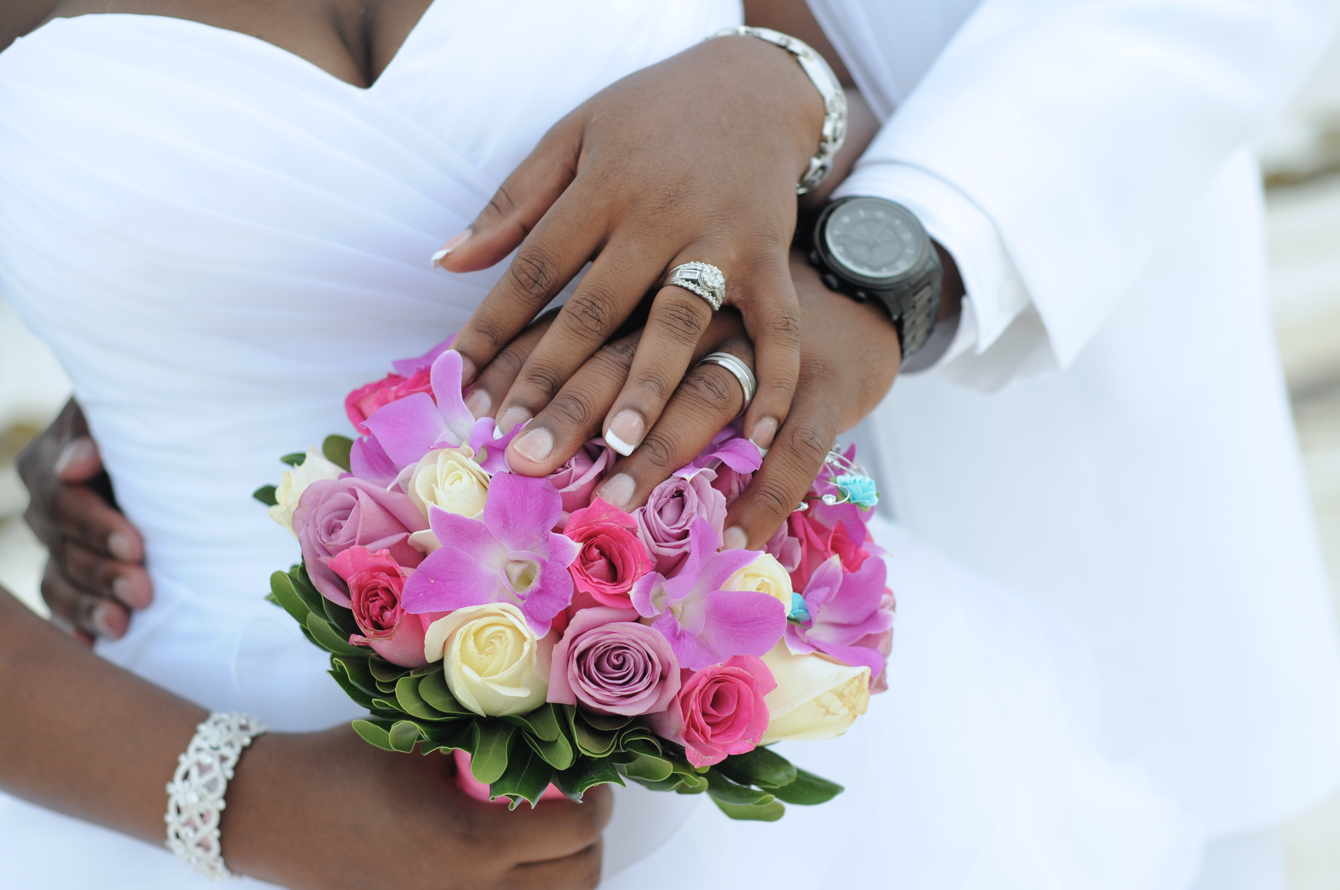 Bride and groom put their hands together on wedding bouquet