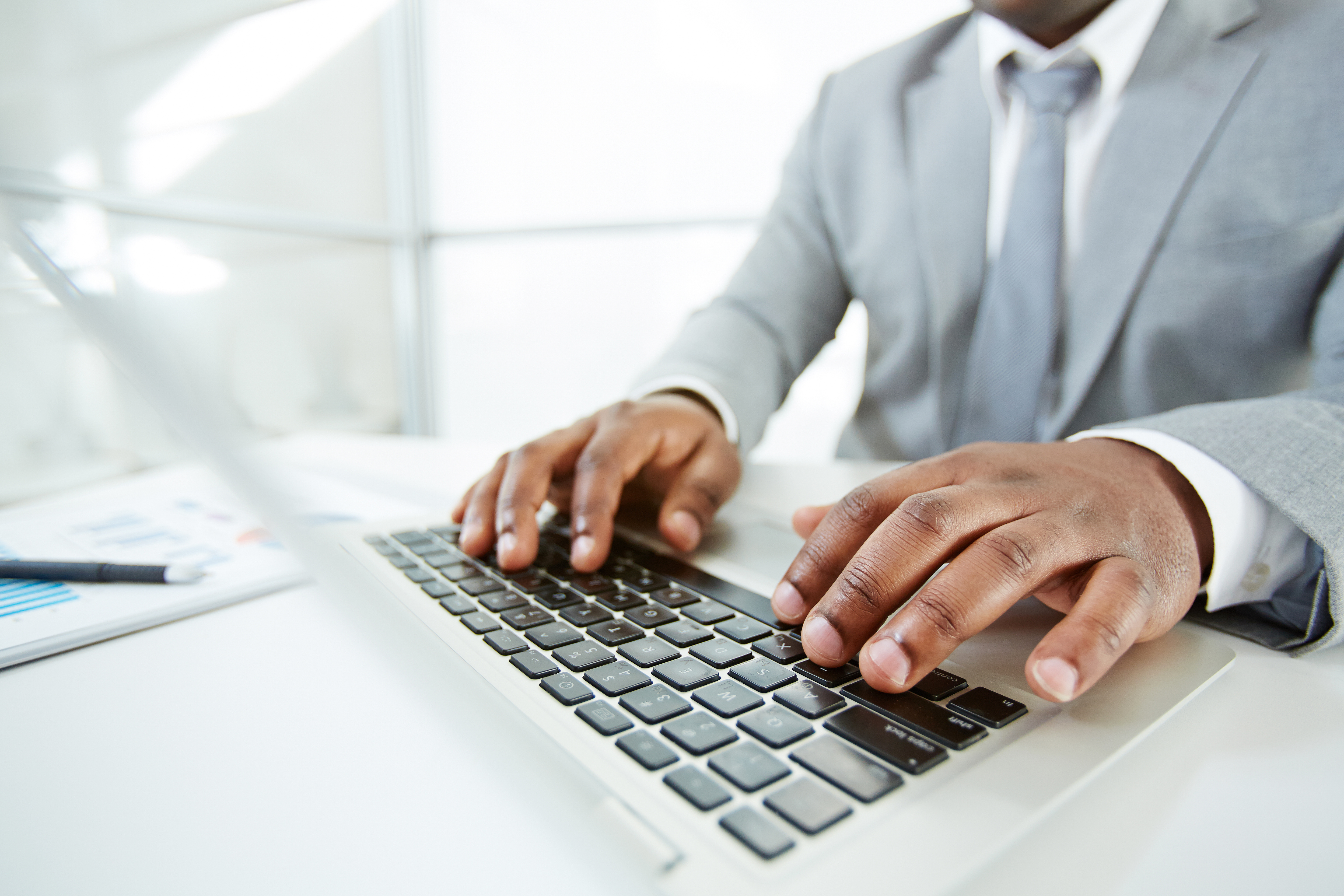 Businessman tapping at a laptop keyboard